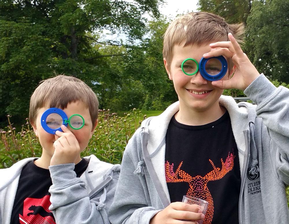 Selv forskerspirer må slappe av og tøyse i sommersola. Et lokk med lupe blir for eksempel nydelige briller… Foto: Lise Mariann Alsli, NTNU Vitenskapsmuseet